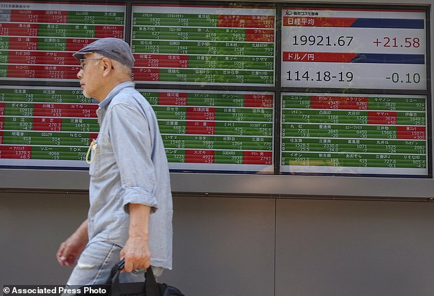 A man walks past an electronic stock board showing Japan's Nikkei 225 index at a securities firm in Tokyo Thursday, May 11, 2017. Asian stocks were moderately higher on Thursday with few data reports to move the markets. Investors are watching tax reform developments in the U.S. after President Donald Trump's firing of the FBI chief.    (AP Photo/Eugene Hoshiko)