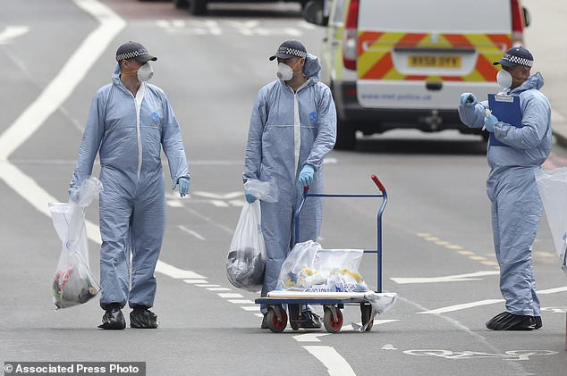 Police forensic officers on London Bridge Sunday June 4, 2017 following Saturday night's terrorist incident. The assault began Saturday night when a van veered off the road and barreled into pedestrians on busy London Bridge. Three men fled the van with large knives and attacked people at bars and restaurants in nearby Borough Market, police and witnesses said. The attack unfolded quickly, and police said officers had shot and killed the three attackers within eight minutes. (Andrew Matthews/PA via AP)