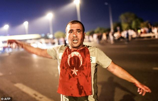 A man covered with blood stands near the Bosphorus bridge as Turkish military clashed with people at the entrance to the bridge in Istanbul last July