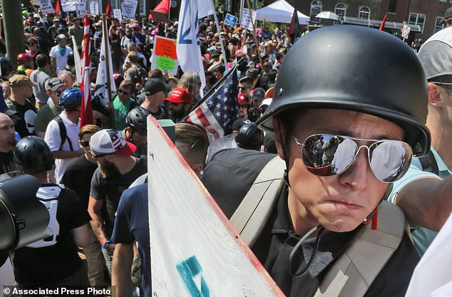 A white nationalist demonstrator with a helmet and shield walks into Lee Park in Charlottesville, Va., Saturday, Aug. 12, 2017.   Hundreds of people chanted, threw punches, hurled water bottles and unleashed chemical sprays on each other Saturday after violence erupted at a white nationalist rally in Virginia. At least one person was arrested.  (AP Photo/Steve Helber)