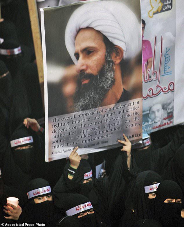 En esta foto de archivo del 30 de septiembre de 2012, un manifestante saudita anti-gobierno lleva un cartel con la imagen del clérigo chií Sheik Nimr al-Nimr encarcelado durante el funeral de tres musulmanes chiítas supuestamente asesinados por las fuerzas de seguridad sauditas en la ciudad oriental De al-Awamiya, Arabia Saudita.  El nuevo príncipe heredero de Arabia Saudí espera transformar el reino y modernizar la sociedad, pero la ejecución planeada de 14 manifestantes chiítas acusados de violencia contra las fuerzas de seguridad sugiere que el manejo del reino de tensiones sectarias y disturbios permanece inalterado.  (Foto AP, Archivo)