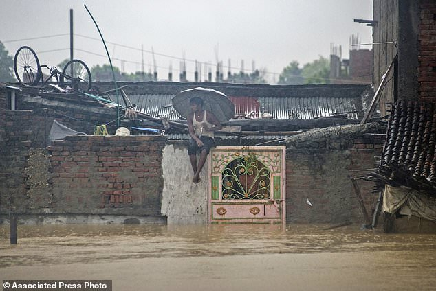 A Nepalese man sits on the wall of his house in a partially submerged village in Birgunj, Nepal, Sunday, Aug. 13, 2017. An official said torrential rain, landslides and flooding have killed dozens of people in Nepal over the past three days, washing away hundreds of homes and damaging roads and bridges across the Himalayan country. (AP Photo/Manish Paudel)