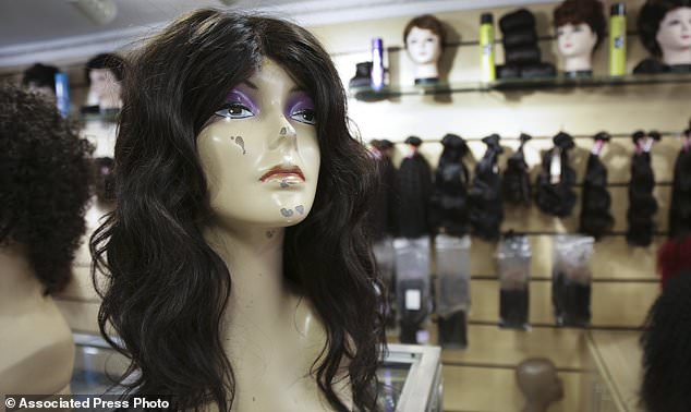 In this photo taken Thursday, Aug. 24, 2017, a wig of natural hair for sale is on display on a mannequin at a hair salon in downtown Nairobi, Kenya. In one of Africa's largest dumps, some residents are making a living by collecting and recycling hair from the mountains of rubbish. (AP Photo/Adelle Kalakouti)