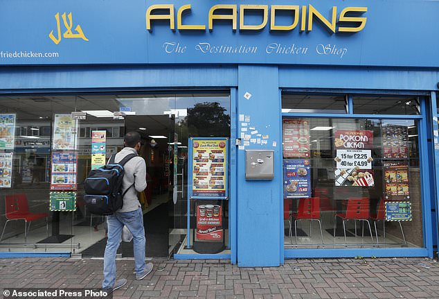 A man walks into Aladdins, a fast food restaurant in Hounslow, London, Monday, Sept. 18, 2017. The two suspects detained over last week's London subway bombing are an 18-year-old refugee from Iraq and a 21-year old believed to be from Syria, both of whom were fostered by a British couple, according to a local official and media reports. The 18-year-old was detained Saturday at the southeast England port of Dover, a departure point for ferries to France. The 21-year-old was held later the same day in Hounslow in west London. (AP Photo/Kirsty Wigglesworth)