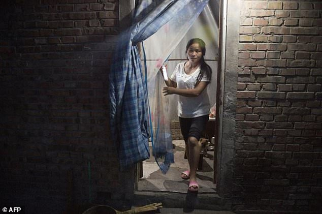 A woman walks out of her room in a migrant village on the outskirts of Beijing