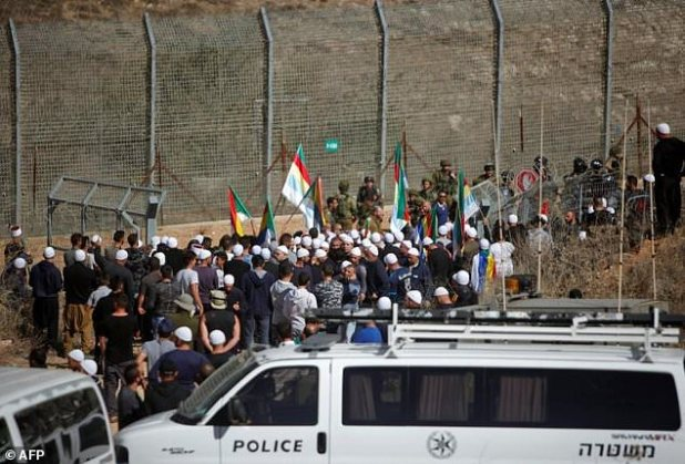 Druze men rally near a barrier that separates the Syrian Golan Heights from the Israeli-occupied side after hearing of clashes in the Syrian part of the plateau of on November 3, 2017