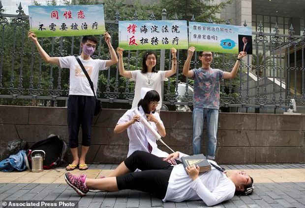 Gay rights campaigners act out electric shock treatment to protest outside a court where the first court case in China involving so-called conversion therapy was held in Beijing in 2014