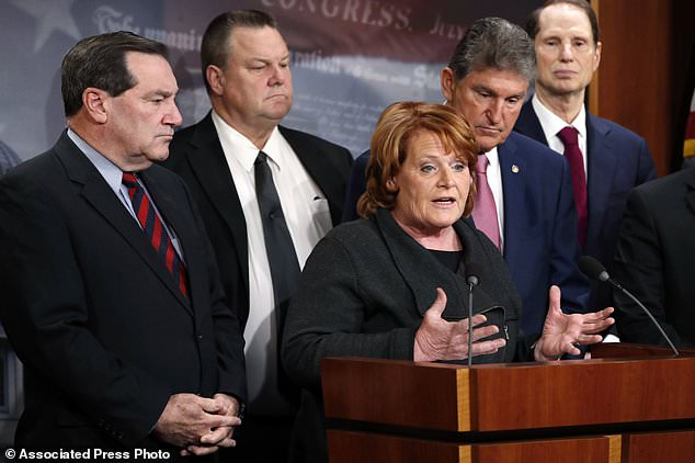Sen. Heidi Heitkamp, D-N.D., speaks, as she is accompanied by Sen. Joe Donnelly, D-Ind., left, Sen. Jon Tester, D-Mont., Sen. Joe Manchin, D-W.Va., and Sen. Ron Wyden, D-Ore., during a news conference about their hopes for a bipartisan approach to tax reform, Tuesday, Nov. 28, 2017, on Capitol Hill in Washington. (AP Photo/Jacquelyn Martin)