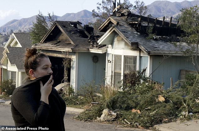 Crystal Shore look over the wildfire damaged neighbors home along Via San Anselmo in the Sylmar area of Los Angeles Wednesday, Dec. 6, 2017. (AP Photo/Chris Carlson)