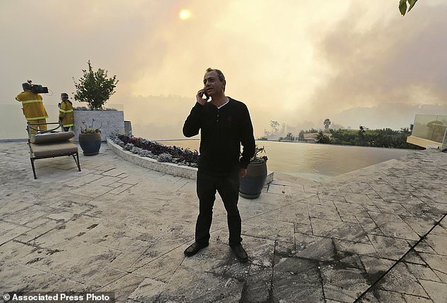 "Maurice Kaboud makes a phone call after a wildfire threatened his home in the Bel Air district of Los Angeles Wednesday, Dec. 6, 2017. When firefighters told Kaboud to evacuate, he decided to stay and protect his home. The 59-year-old stood in the backyard of his multimillion- dollar home as the Skirball fire raged nearby. ""God willing, this will slow down so the firefighters can do their job,"" Kaboud said. (AP Photo/Reed Saxon)"