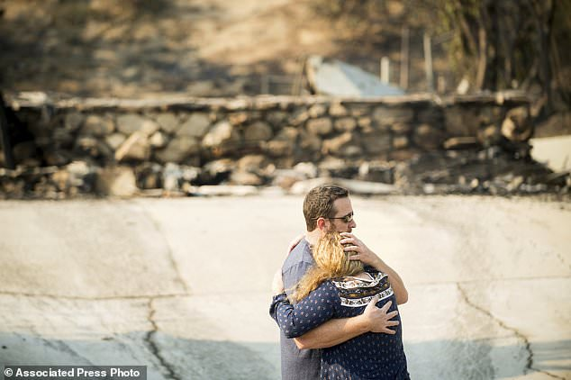 Paul and Erica Mattesich embrace before sifting through rubble at their Ventura, Calif., home on Wednesday, Dec. 6, 2017. The family lost their house when the Thomas fire tore through their neighborhood on Colina Vista. (AP Photo/Noah Berger)