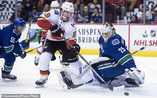 Vancouver Canucks defenseman Alex Biega (55) looks on as Calgary Flames left wing Matthew Tkachuk (19) tries to get a shop past Canucks goalie Jacob Markstrom (25) during first period NHL hockey action in Vancouver, British Columbia, Sunday, Dec. 17, 2017. (Jonathan Hayward/The Canadian Press via AP)