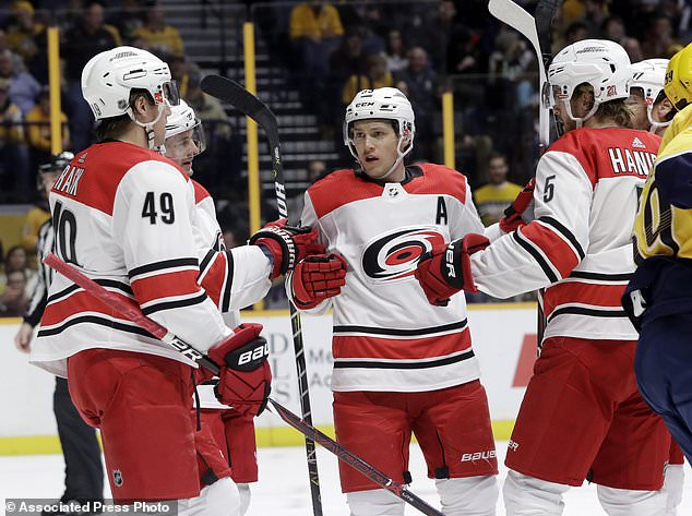 Carolina Hurricanes defenseman Noah Hanifin (5) celebrates with Victor Rask (49), of Sweden, and Jeff Skinner, center, after Hanifin scored a goal against the Nashville Predators during the first period of an NHL hockey game Thursday, Dec. 21, 2017, in Nashville, Tenn. (AP Photo/Mark Humphrey)