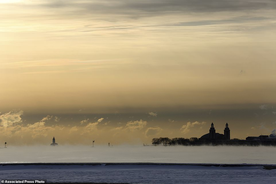 Lake Michigan is pictured above on Tuesday steaming in the morning as temperatures dipped below zero at North Avenue Beach