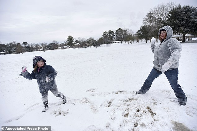 Snow began falling during the pre-dawn hours Tuesday in Louisiana, where freeways were closed in and around Baton Rouge (Pictured,Savannah Stucker, left, and Loretta Compton throw snow balls at Betty Virginia Park in Shreveport, Louisiana)