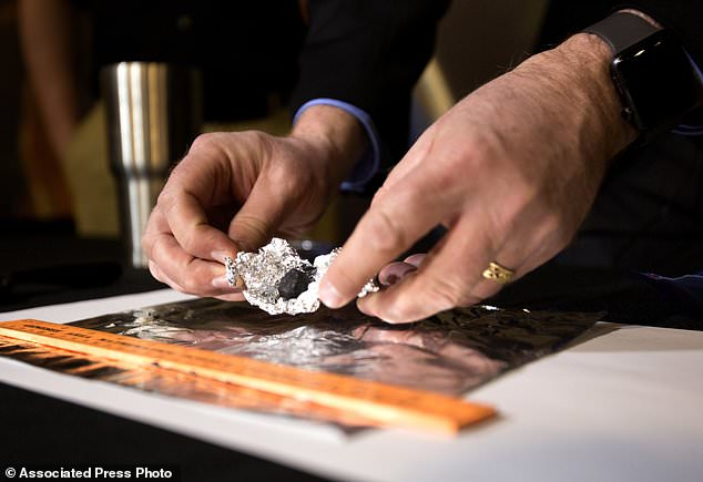 Meteorite hunters seek permission from landowners before searching on their property. Astronomer Todd Slisher unfolds tin-foil to reveal a piece of stony-iron meteorite
