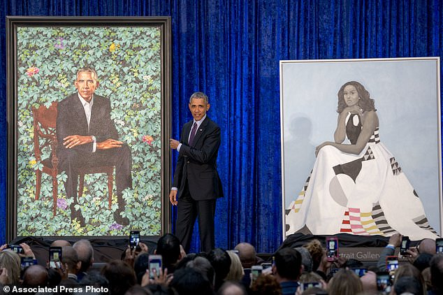 Former President Barack Obama, center, stands on stage during the unveiling of the Obama's official portraits at the Smithsonian's National Portrait Gallery, Monday, Feb. 12, 2018, in Washington. (AP Photo/Andrew Harnik)