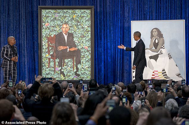 Former President Barack Obama, right, and Artist Kehinde Wiley, left, unveil the Obama's official portraits at the Smithsonian's National Portrait Gallery, Monday, Feb. 12, 2018, in Washington. (AP Photo/Andrew Harnik)