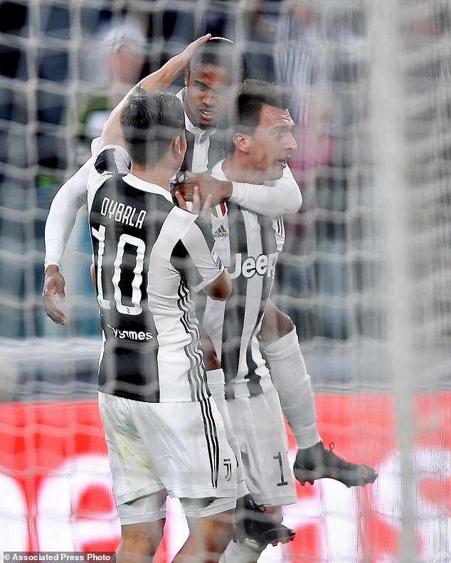 Juventus's Mario Mandzukic, right, celebrates with teammates Douglas Costa, top, and Paulo Dybala after scoring his side's first goal during the Italian Serie A soccer match between Juventus and Sampdoria at the Allianz Stadium in Turin, Italy, Sunday, April 15, 2018.  (Alessandro Di Marco/ANSA via AP)