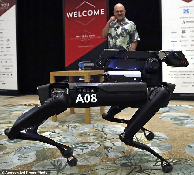 Boston Dynamics SpotMini robot is walks through a conference room during a robotics summit in Boston. It's never been clear whether robotics company Boston Dynamics is making killing machines, household helpers, or something else entirely