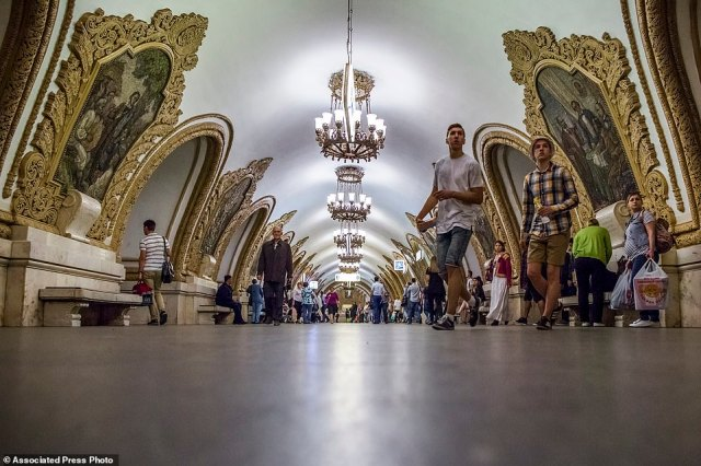 The Kievskaya Metro station in Moscow on the circle line. The walls are adorned with Soviet-era artwork while ornate chandeliers hang from the ceiling