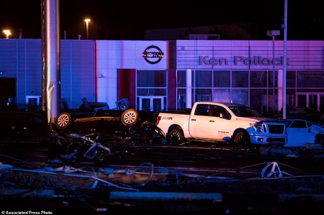 Cars were overturned and damaged in the strong winds at the mall, which was pounded by the force of the storm, pictured above Wednesday night after the storm calmed