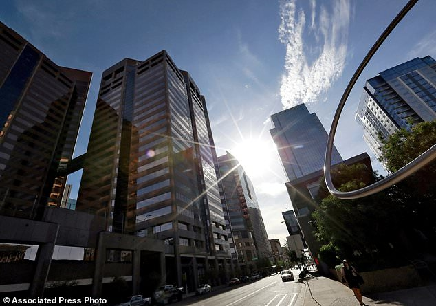 "In this Monday, July 23, 2018 photo, the sun beats down on downtown Phoenix. Already devilishly hot for being in the Sonoran desert, Arizona's largest city is also an ""urban heat island,"" a phenomenon that pushes up temperatures in areas covered in heat-retaining asphalt and concrete. Phoenix officials say they are tackling urban warming, monitoring downtown temperatures, planting thousands of trees and capturing rainwater to cool off public spaces. (AP Photo/Matt York)"