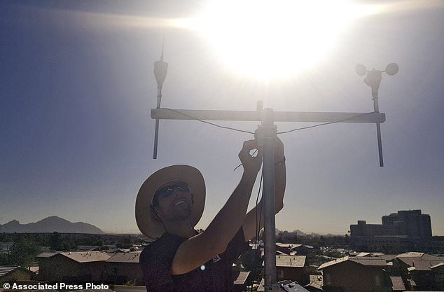 In this July 20, 2018 photo provided by Edison-Eastlake Measurement Campaign, David Hondula, Assistant Professor in the School of Geographical Sciences and Urban Planning at Arizona State University and a faculty affiliate of the Urban Climate Research Center, works on a weather station installation in the Aeroterra Apartment community in Phoenix. David Sailor, director of Arizona State University's Urban Climate Research Center, and his team are working with Phoenix to monitor urban warming in a low-income neighborhood sandwiched between a freeway and a hospital. (David Sailor/Edison-Eastlake Measurement Campaign via AP)