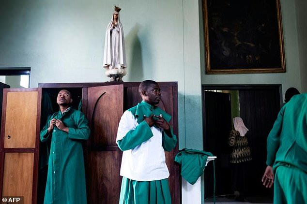 Altar boys prepare themselves ahead of Sunday Mass at the Sacred Heart Church in Harare