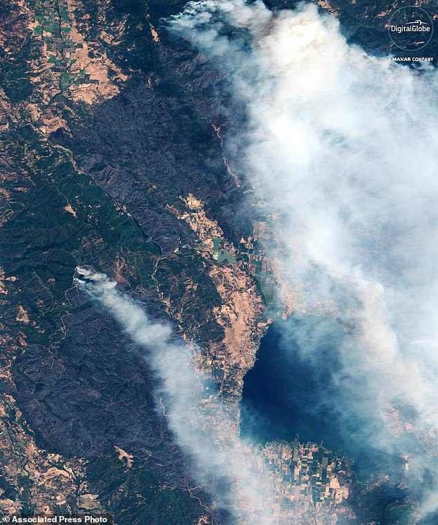 "This Monday, August 6, 2018, digital image of DigitalGlobe shows smoke from the ""River Fire"", left, and the ""Ranch Fire,"" above, to Clear Lake, California. The dark brown areas in the middle show burnt vegetation. Bottom right is Clear Lake. (Satellite image © 2018 DigitalGlobe, a maxar company via AP)"