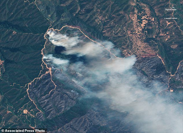 "This satellite image, provided by DigitalGlobe, shows clouds of smoke from the ""River Fire"" burning vegetation west of Clear Lake, California. The dark brown areas in the center, surrounded by lighter bulldozed trails, show burnt vegetation around the South Cow Mountain Recreation area. (Satellite image © 2018 DigitalGlobe, a Maxar company, via AP)"
