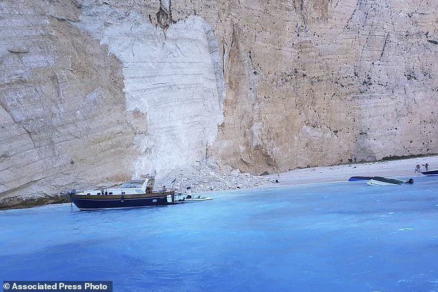 Small boats capsize after a landslide on the popular beach of Navagio, or Shipwreck Beach, on the western island of Zakynthos, Greece, Thursday, September 13, 2018. Greek authorities say a landslide on a popular beach on the western island of Zakynthos had at least one injury Episode while the Coast Guard was trying to figure out if people were missing. (imerazante.gr via AP)