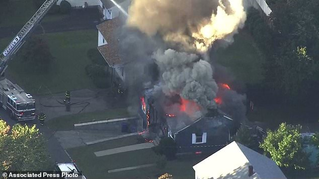In this image from the WCVB video in Boston, firefighters in Lawrence, Mass, a suburb of Boston, Thursday, September 13, 2018, are fighting a raging house fire. Emergency crews respond to what they believe is a series of gas explosions that have damaged homes in three communities north of Boston. (WCVB via AP)