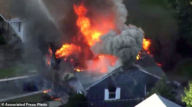 In this image take video of WCVB in Boston, flames burn a house in Lawrence, Mass, a suburb of Boston, Thursday, September 13, 2018. Emergency teams respond to what they believe is a series of gas explosions that have damaged Houses in three communities north of Boston. (WCVB via AP)
