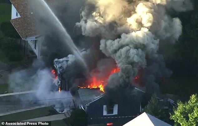 In this image take video of WCVB in Boston, flames burn the roof of a house in Lawrence, Mass, a suburb of Boston, Thursday, September 13, 2018. Emergency teams react to what they believe is a series of gas explosions that Houses in three communities north of Boston have been damaged. (WCVB via AP)