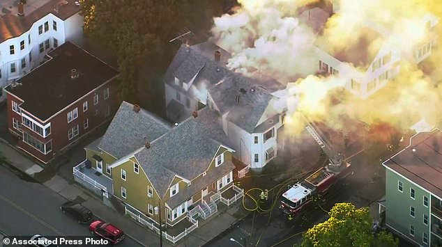 In this image from the video of WCVB in Boston, firefighters in Lawrence, Mass, a suburb of Boston, Thursday, September 13, 2018, are fighting a large fire building. Emergency crews respond to what they believe is a series of gas explosions that have damaged homes in three communities north of Boston. (WCVB via AP)