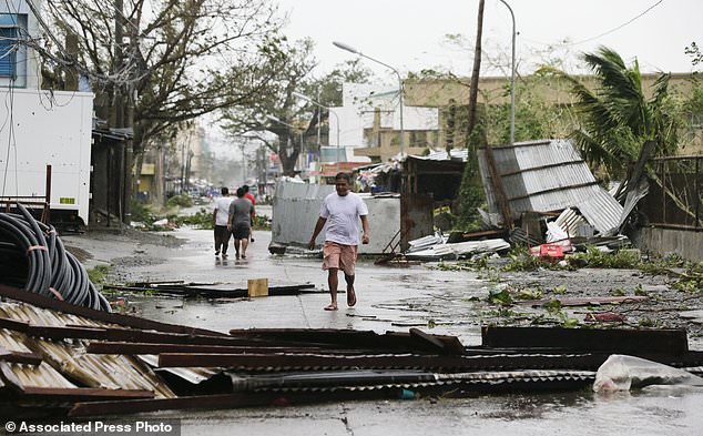 A resident walks beside toppled structures as Typhoon Mangkhut barreled across Tuguegarao city in Cagayan province, northeastern Philippines early Saturday, Sept. 15, 2018. The typhoon slammed into the Philippines northeastern coast early Saturday, it's ferocious winds and blinding rain ripping off tin roof sheets and knocking out power, and plowed through the agricultural region at the start of the onslaught. (AP Photo/Aaron Favila)