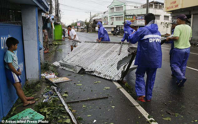 Workers carry tin roof sheets that was blown by strong winds from Typhoon Mangkhut as it barreled across Tuguegrao city in Cagayan province, northeastern Philippines on Saturday, Sept. 15, 2018. The typhoon slammed into the Philippines northeastern coast early Saturday, it's ferocious winds and blinding rain ripping off tin roof sheets and knocking out power, and plowed through the agricultural region at the start of the onslaught. (AP Photo/Aaron Favila)