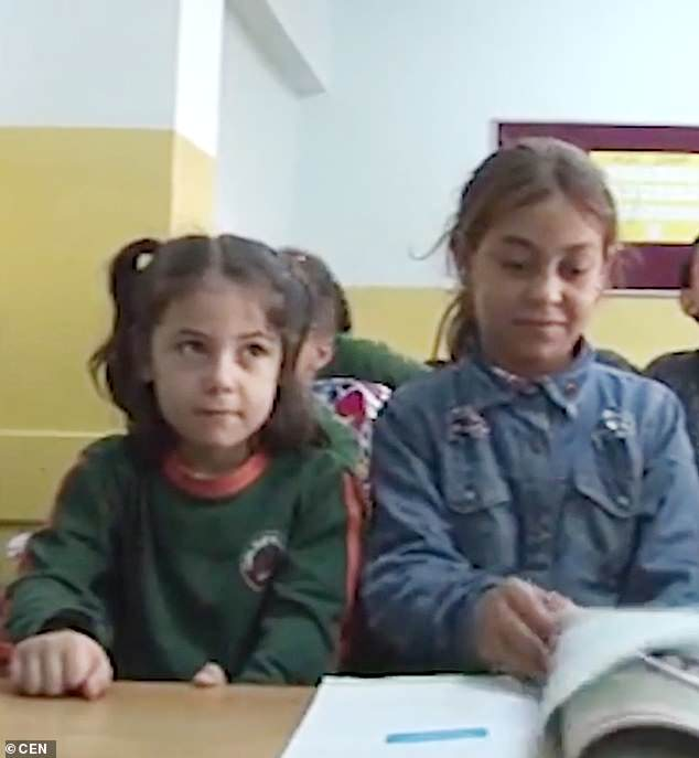 Halime (right) now has a place at a Turkish school and is pictured attending class
