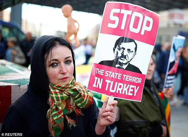 "A protester takes part in a demonstration organised by a group calling itself ""Erdogan Not Welcome"" during the visit of Turkish President Tayyip Erdogan in Berlin"