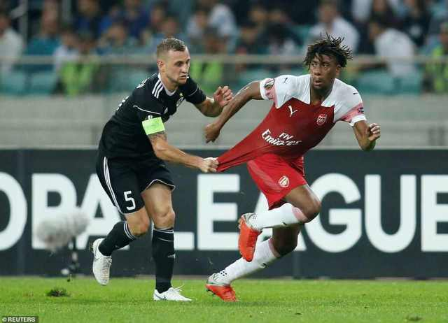 Iwobi is held back by Qarabag captain Maksim Medvedev, who is shown a yellow card for his foul in the first half