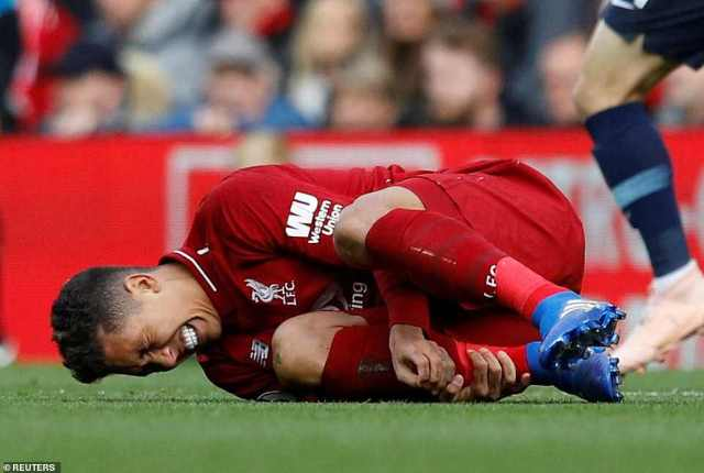 Roberto Firmino clutches his leg after being fouled in his own half following a counter attack by Liverpool