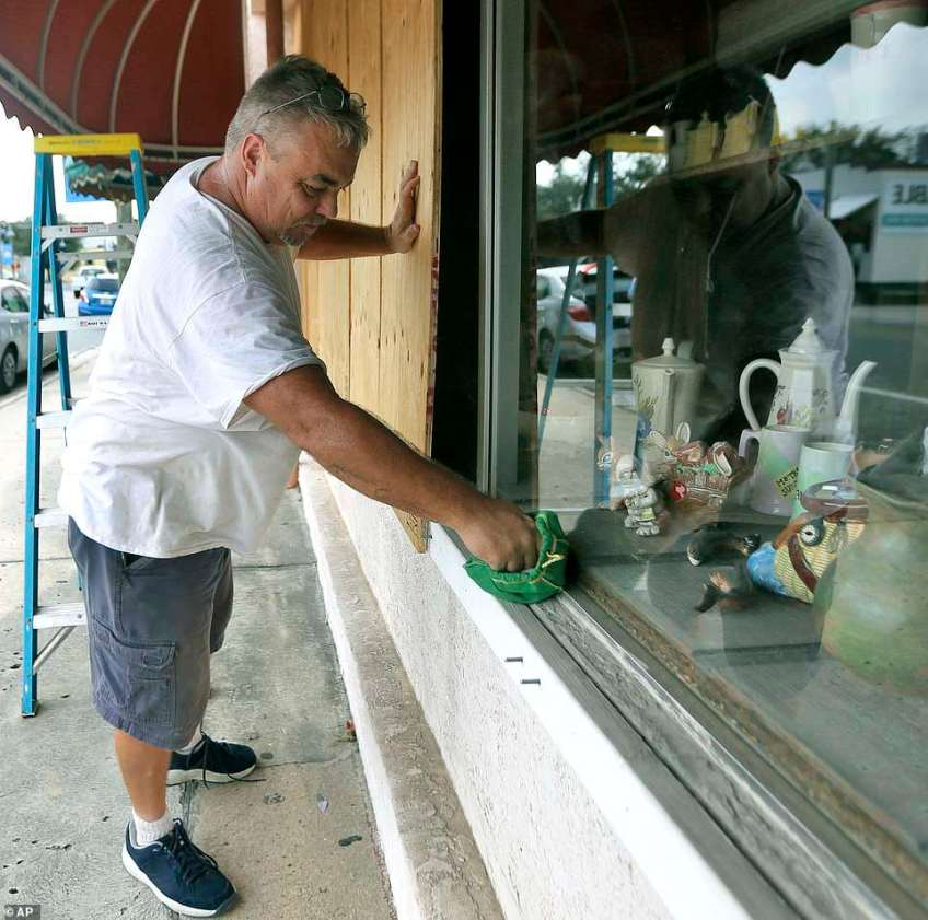 Bobby Smith boards up the windows at Jani's Ceramics in Panama City, Florida on Mondayin preparation for the arrival of Hurricane Michael