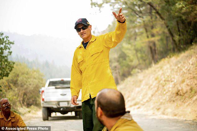 Der Feuerwehrmann Phil Tapscott, ein Task Force Leiter des Mendocino Complex Fire, spricht mit einer Crew aus Montana am Mittwoch, den 8. August 2018, im Mendocino National Forest, Kalifornien. Feuerwehrmänner aus Australien und Neuseeland helfen Kalifornien, diese Woche anzukommen im Mendocino Complex Fire nach einem 8,600 Meilen (13,840 Kilometer) Flug und einer zweistündigen Busfahrt. (AP Foto / Noah Berger)