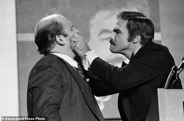 FILE - Dans cette photo d'archives du 2 décembre 1977, l'acteur Burt Reynolds, à droite, pince les joues de l'humoriste Dom Deluise lors d'un rôti de Reynolds à Atlanta. Reynolds, qui a joué dans des films dont
