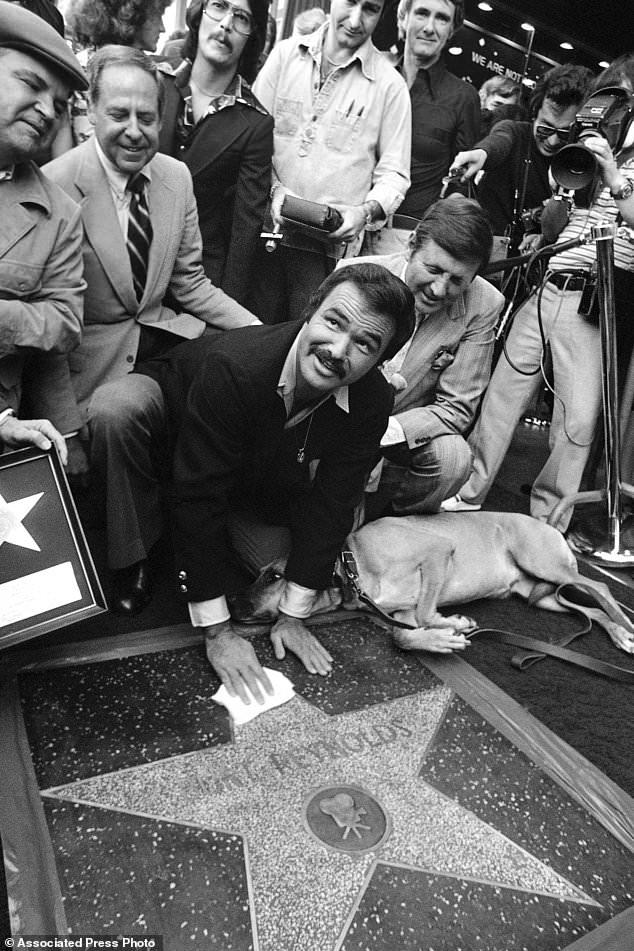 FILE - Dans cette photo d'archives du 15 mars 1978, l'acteur Burt Reynolds peaufine la star dévoilée dans le Hollywood Walk of Fame à Los Angeles. Reynolds, qui a joué dans des films dont