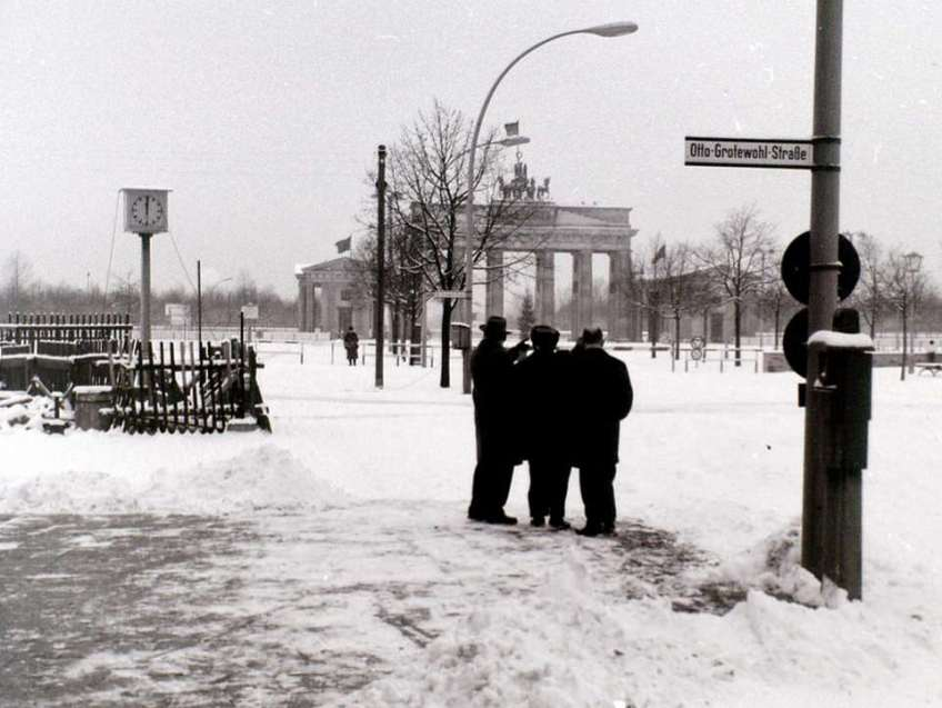 Unter den Linden in East Berlin at Christmas 1964. This shot looks westwards towards the Brandenburger Tor from the approximate location of the present-day Hotel Adlon. The pre-war Adlon was one of the great hotels of Europe, but was largely destroyed in 1945. At the time of this photograph the remains of the hotel, still functioning, lay off-camera to the left of the pillar clock, and the edifice was so near to the Berlin Wall that the windows on the western side were heavily festooned with metal bars. Otto-Grotewohl-Strasse was named after the first East German Prime Minister, who died three months before this photograph was taken