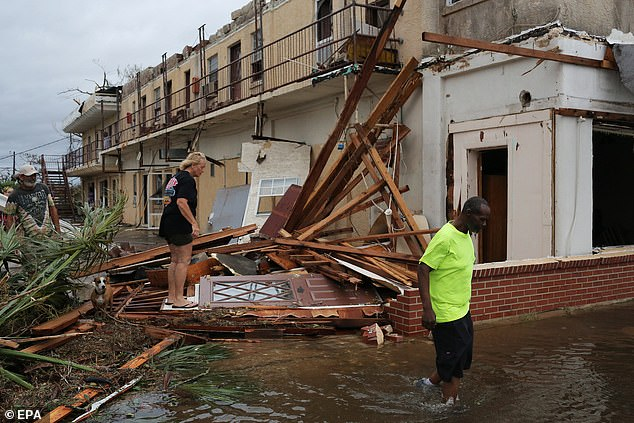People survey the damage to a building in Panama City, Florida. There have been disruptions at airports closer to where the hurricane hit