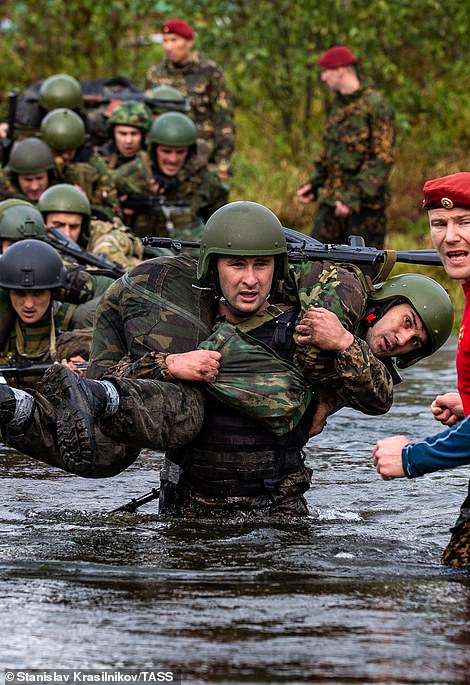 Soldiers prove their strength by carrying a comrade over a deep section of water, balancing them on their shoulders