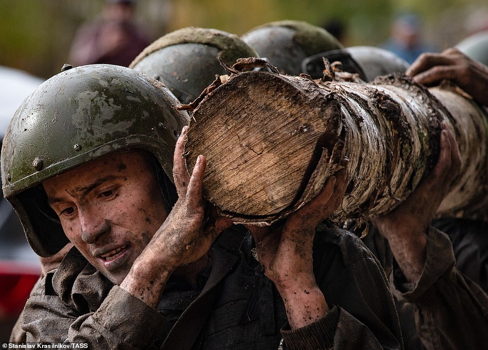 Contenders soaked in water and covered in mud work together to carry a thick log during the five-mile cross country test